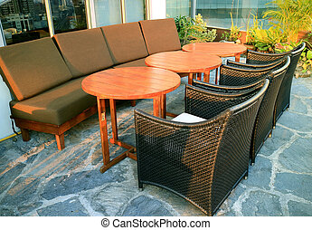 Empty sofas and chairs with round tables at the rooftop terrace