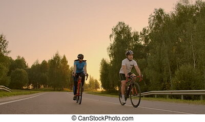 Empty Space. Sporty friends on bicycle on sunset. Couple...