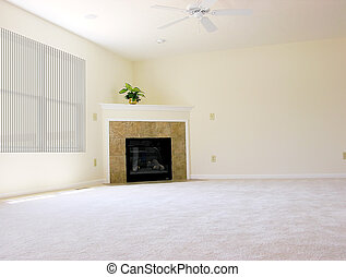 Spacious family room in an empty house. Everything is gone except one lonely plant above the fireplace in the corner, a ceiling fan and the window covering. A house is not a home without a family.