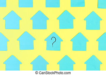 Empty stickers in the shape of a house on a yellow background. In the center is a blue sticker with a question mark written on it. Photo.