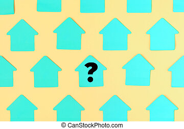 Empty stickers in the shape of a house on a yellow background. In the center is a turquoise sticker with a question mark. Photo.
