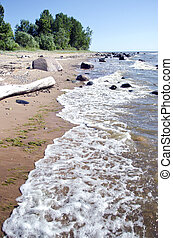 empty summer resort beach with stones and waves