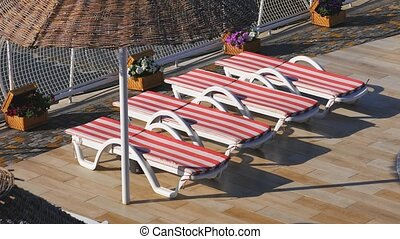 Empty sunbeds near the hotel and the beach. Morning on a beach, Beach with sun loungers and sun umbrellas.
