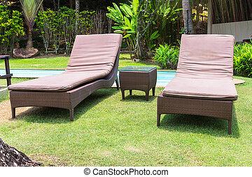 Empty sunbeds on green grass in summer