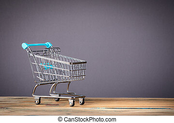empty supermarket shopping cart on grey background with copy space