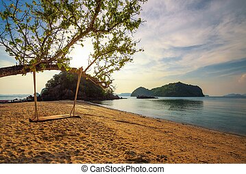 Empty swing at a beach in Thailand at sunset