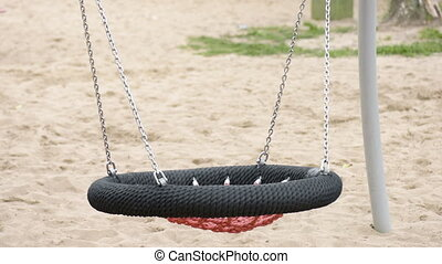 Empty swing at playground - Abandoned empty swing swaying in...
