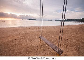 Empty swing on the beach