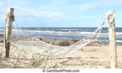 Empty swinging hammock in a sandy beach with wavy sea water...