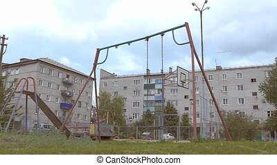 empty swings swaying in the courtyard of slow motion video -...
