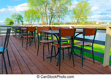 Empty tables in a cafe by the river