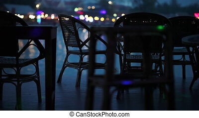 The empty tables in the bar on the waterfront with people passing in the background