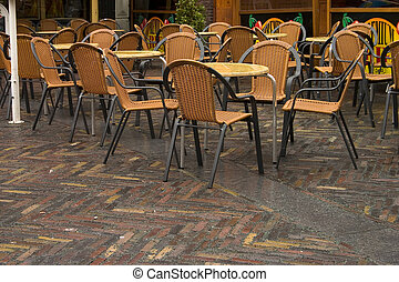 Empty terrace - A group of wet restaurant chairs sit...