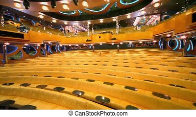 Empty theater with rows of yellow sofas, around motion