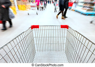 Empty trolley in supermarket or mall full of crowded people....
