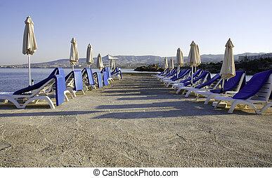 Empty tropical beach chairs.