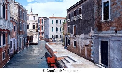 Empty venetian gondola on a canal in Venice, Italy - Empty...