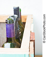 Empty vine bottles in wooden crate.
