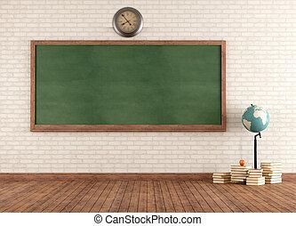 Empty vintage classroom with green blackboard against brick ...