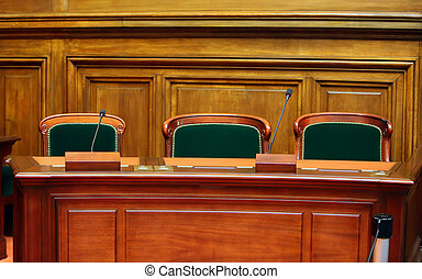 Empty vintage court's room with table, chairs and microphones.