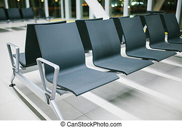 Empty waiting area of the airport with seats in a row at night. Waiting at the airport. Conceptual photo.