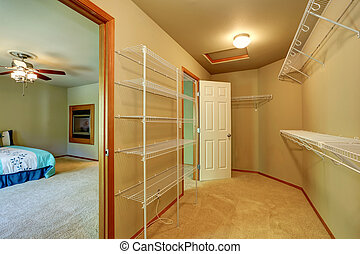 Empty walk through closet with shelves in the bedroom.