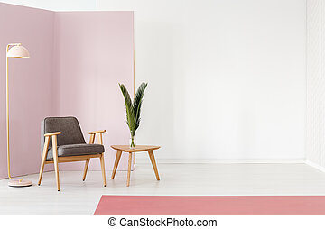 Empty wall next to armchair