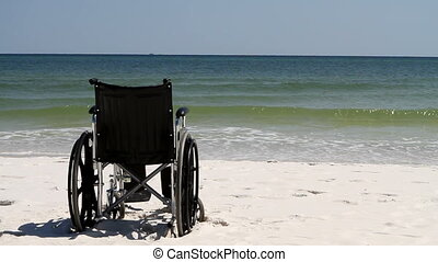 Wheelchair sits empty in the sand on the beach with waves breaking on the shore in the background.