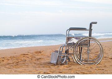 empty wheelchair on beach - an empty wheelchair parked on...