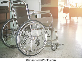 Empty wheelchair parked in hospital hallway with light hope concept