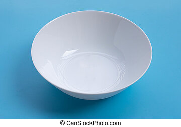 Empty white bowl on blue background.