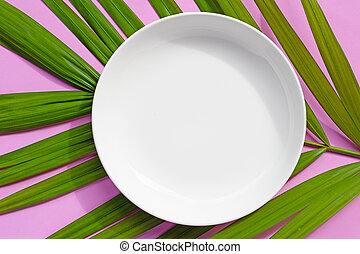 Empty white ceramic plate on tropical palm leaves on pink background.