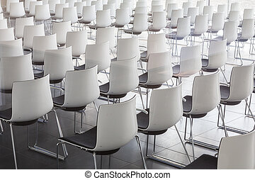 Empty white chairs in contemporary conference hall with