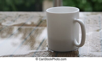 Empty white cup of coffee on a table in rain water