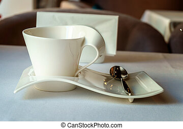 empty white Cup on a white plate of unusual form with teaspoon