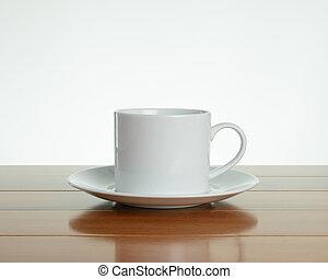 Empty white mug with saucer on wood