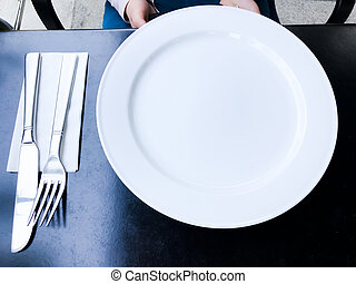 empty white plate on black table with knife and fork
