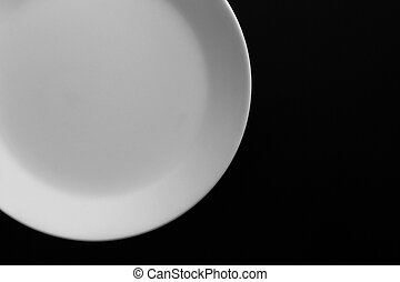 Empty white plate on black wooden table