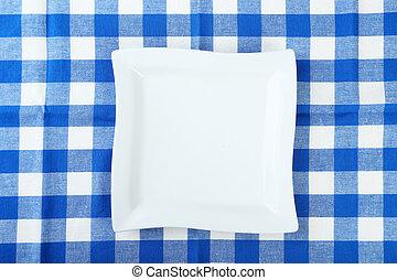 Empty white plate on blue napkin
