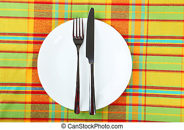 Empty white plate on colorful napkin