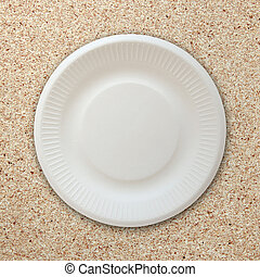 empty white plate on cork board background