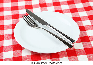 Empty white plate on red napkin