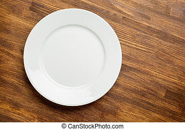 empty white plate on wooden background top view.