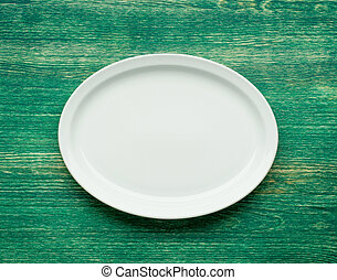 Empty white plate on wooden table. Flat lay.