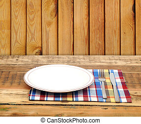 Empty white plate with fork and knife on wooden table