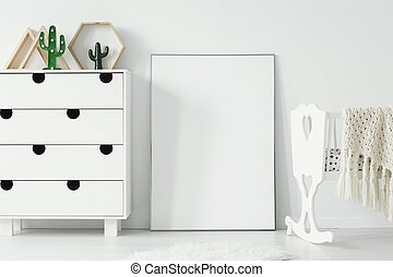 Empty white poster with mockup between cabinet and cradle in baby's room interior. Real photo