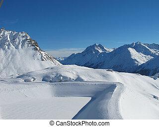 Empty winding ski run on sunny winter day