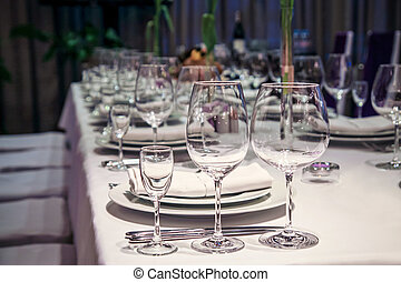 Empty wine glasses arranged on a table in an open air...