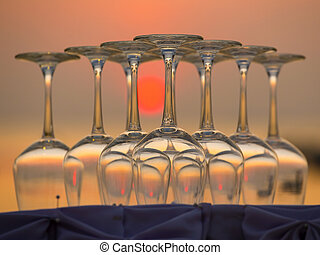 Empty wine glasses during sunset on the beach in a restaurant, Thailand