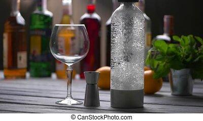 Empty wineglass beside bottle. Bubbles in transparent...